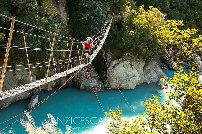 Female tramper crossing a swingbridge over Whataroa River Gorge - South Westland, West Coast, New Zealand MR