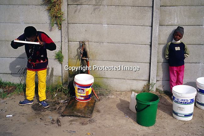 children,tap,street,poverty,township,bucket,.Children collects water at a tap in Khayelitsha, the biggest and poorest township outside Cape Town, South Africa..©Per-Anders Pettersson/iAfrika Photos