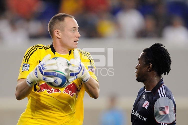New York Red Bulls goalkeeper Greg Sutton (24) controls the ball under pressure from Kenny Mansally (7) of the New England Revolution. The New York Red Bulls defeated the New England Revolution 2-1 during a Major League Soccer (MLS) match at Red Bull Arena in Harrison, NJ, on June 10, 2011.