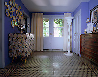 A hall table decorated in yellow enamel flowers has been placed on one side of the geometric floor in the entrance hall opposite a plan chest