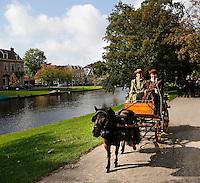 Ringsteken met paard en wagen tijdens Alkmaar Ontzet in het Kennemerpark in Alkmaar. Mensen zijn gekleed in klederdracht