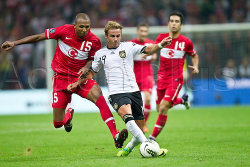 07.10.2011 Istanbul Turkey.  Germany's Mario Goetze (C) and Turkey`s Mehmet Aurelio (L) and Arda Turan (R) vie for the ball during the EURO 2012 qualifying match between Turkey and Germany at the Turk Telekom Arena.