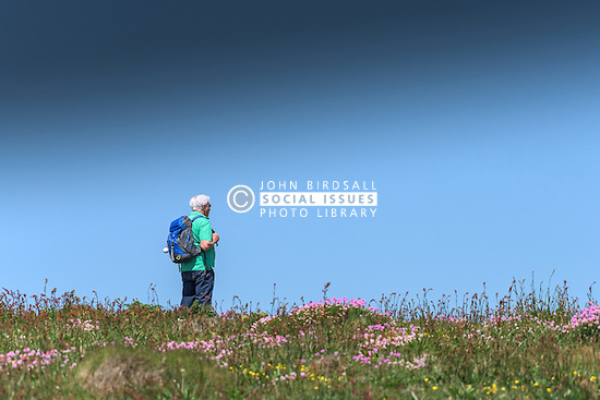 A walker enjoys the view from East Pentire Headland in Newquay, Cornwall.