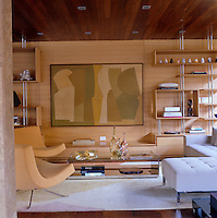 The open-plan oak panelled living room has a pair of Verner Panton pendant lights and Pop chairs by Ligne Roset