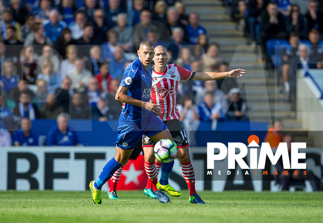 Oriol Romeu of Southampton plays a pass under pressure from Islam Slimani of Leicester City during the Premier League match between Leicester City and Southampton at the King Power Stadium, Leicester, England on 2 October 2016. Photo by Andy Rowland.