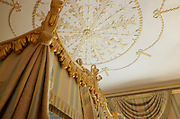 A detail of a decorative gilded ceiling above the top of an ornate four-poster bed.