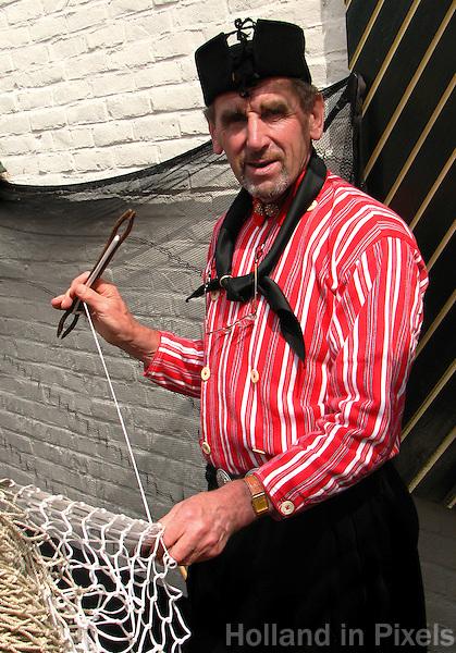 Tijdens Urkerdag lopen de inwoners in klederdracht . Visser repareert een net
