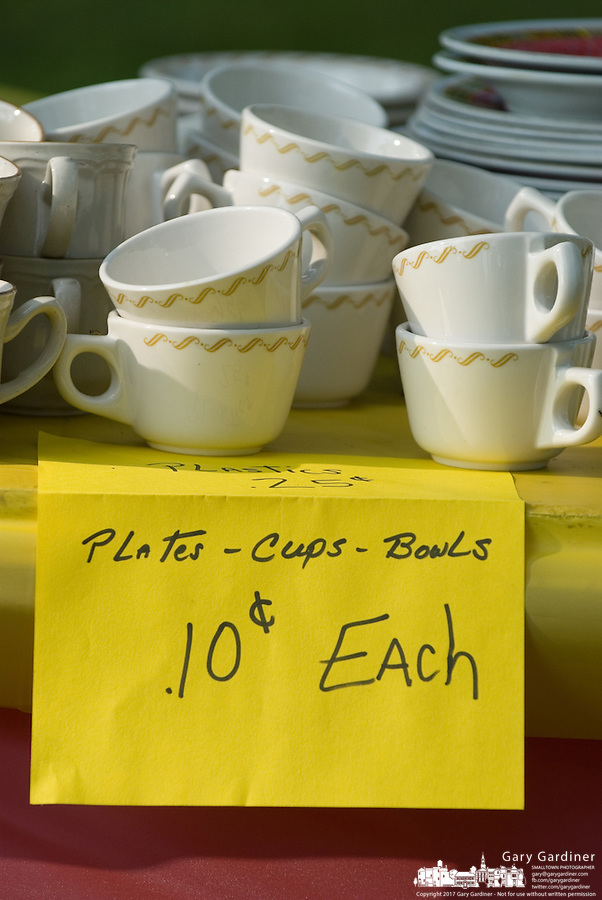 A hand written sign prices plates, cups, and bowls at a rural yard sale on a farm near West Liberty, Ohio.<br />