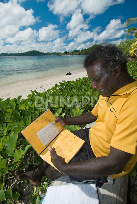 """As soon as he could write, Evans Zama, a clan leader of the Volaikana tribe, has been recording oral histories which stretch back 8 generations. He has compiled several handwritten volumes that document his family tree, land rights, locations of tombs, etc. Volaikana, he says, means """"war survivors"""", explaining that his people evacuated a broad area due to headhunting threats. Some of the property that British colonials and the Solomons government designated as """"alienated lands"""" (including the Arnavon Islands) were once owned by the Volaikana, he says."""