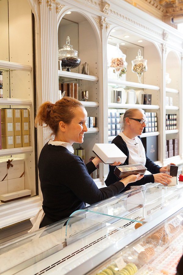 Saleswomen engage with customers at Angelina, Rivoli Street, Rue de Rivoli, Paris, France, Europe
