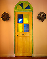 This glass-panelled door has a hand-painted frame annd is flanked by a pair of bronze wall lights