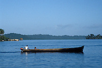 Man and boy in a motorized boat near the town of Bocas del Toro, Isla Colon, Panama