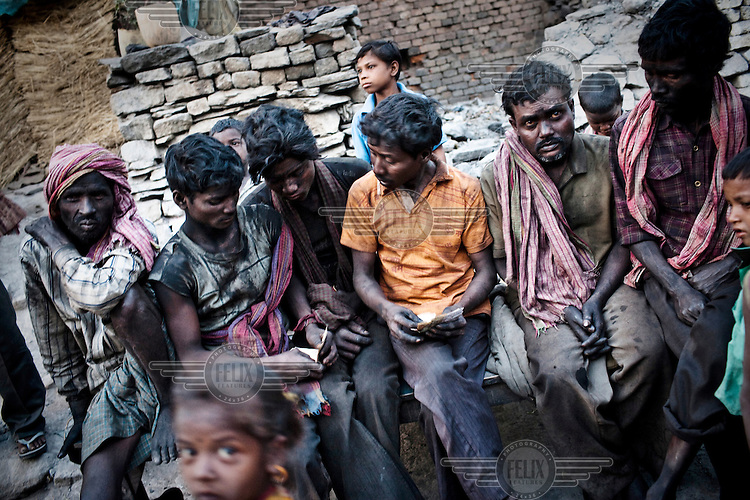 After a day of tiring labour, miners gather in the centre of Bokapahari village to be paid. They work for about 10 hours a day, loading coal trucks in the BCCL coal mines, for which they receive 150 Indian Rupees (3.5USD).