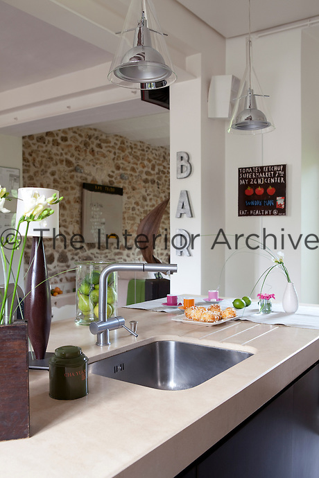 In the open plan kitchen a stainless-steel sink is set into the stone work surface with two contemporary pendant lights above