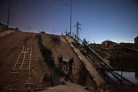 Syria, Deir az-Zor, 2013/03/19..While goverment loyal sniper targeting the bombed and damaged Ganamat bridge across the Eurphrates river, people take risks to get supplies into Deir az-Zor. Crossing at night is much safer..Syrie, Deir ez-Zor, 19/03/2013.Alors que les snipers loyaux au gouvernement prennent pour cible le pont Ganamat sur l'Euphrate, bombardé et détruit, les habitants prennent tous les risques pour s'approvisionner dans Deir ez-Zor. La traversée de nuit est beaucoup plus sûre.  .Photo: Timo Vogt / Est&Ost Photography.