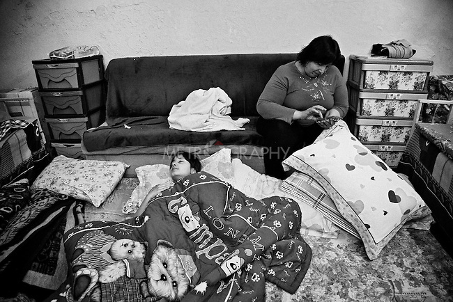 4.4..2015, Kirkuk,Iraq: Time to sleep for Marta, while her mother is busy sending a text message to her sister in Baghdad.