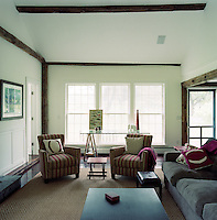 The contemporary house has been designed with elements echoing the colonial style traditional to the Hudson Valley such as the trio of old-fashioned sash windows and the weathered beams of the walls and ceiling in the living room