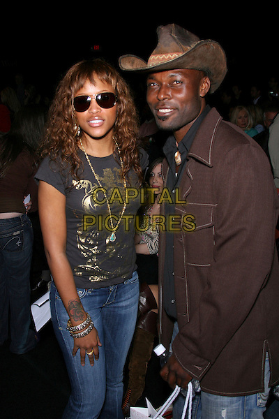 EVE & JIMMY JEAN-LOUIS.Mercedes-Benz Fall 2006 L.A. Fashion Week - DAY 3 - Arrivals held at Smashbox Studios, Culver City, California, USA.  .March 21st, 2006.Photo: Zach Lipp/AdMedia/Capital Pictures.Ref: ZL/ADM.half length black top necklace sunglasses shades jeans denim brown jacket cowboy hat stetson.www.capitalpictures.com.sales@capitalpictures.com.© Capital Pictures.
