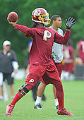 Washington Redskins quarterback Robert Griffin III, wearing a brace on his surgically reconstructed knee, looks to pass as he participates on the sidelines during last day of OTAs at Redskins Park in Ashburn, Virginia on Thursday, June 6, 2013.<br /> Credit: Ron Sachs / CNP