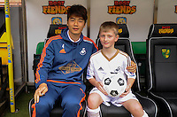 Ki Sung-yueng of Swansea City with the matchday mascot during the Barclays Premier League match between Norwich City and Swansea City played at Carrow Road, Norwich on November 6th 2015