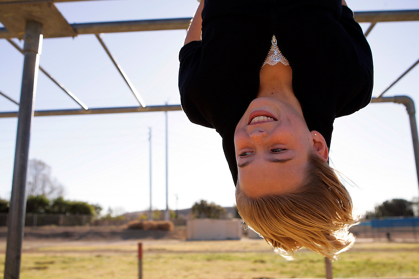 A young girl hangs upside down on the monkey bars on a playground in Thousand Oaks, California.
