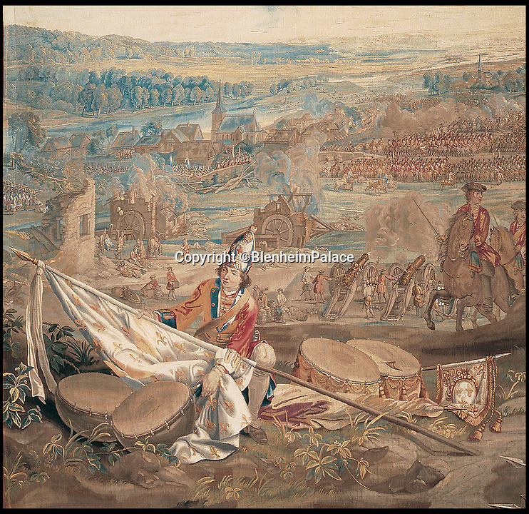 BNPS.co.uk (01202 558833)<br /> Pic: BlenheimPalace/BNPS<br /> <br /> The Battle of Blenheim tapestry shows a Grenadier Guard furling the captured Royal French flag.<br /> <br /> Blenheim Palace prepares to pay its Royal dues&hellip;.Historic standard of the 'Sun King' is presented annually to the Queen in lieu of rent.<br /> <br /> The 300 year old tradition will be upheld this week when officials from Blenheim Palace travel to Windsor Castle.<br /> <br /> Each year representatives of the Duke of Marlborough present a French royal standard to the Superintendent of the Castle in lieu of rent.<br /> <br /> Only Blenheim Palace and the Duke of Wellington's estate at Stratfield Saye are afforded the 'Quit rent standard' in thanks for their respective victories over the old enemy, France.<br /> <br /> Blenheim's standard is always presented in the week leading up to the anniversary of the First Duke&rsquo;s historic victory over Louis XIV at the Battle of Blenheim on August 13, 1704.<br /> <br /> Although Blenheim Palace was paid for by public subscription, the land it is on was a former Royal hunting lodge and in theory if the standards are not delivered the Queen could reclaim her former estate.