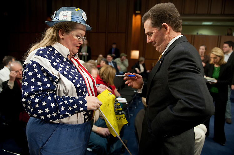 "UNITED STATES - JANUARY 27: Sen. Jim DeMint, R-S.C., signs a ""Don't Tread On Me"" flag for JoAnn Abbott, of the Washington, DC Tea Party, as he arrives for the first meeting of the Senate Tea Party Caucus in the HartSenate Office Building on Thursday, Jan. 27, 2011. (Photo By Bill Clark/Roll Call)"