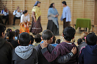 """Two boys have their arms around each other as they watch a performance by Roma or gypsy theater Romathan in """"Dwarf"""" at the Banske Elementary School with a Roma or gypsy majority student body in Banske, Slovakia on June 2, 2010."""