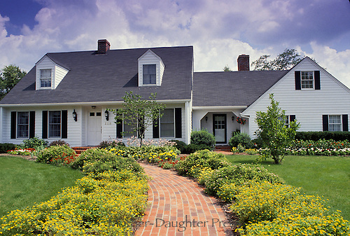 White Cape cod style house with welcoming walk way lined with yellow flowers to the front door, Summer, Midwest USA