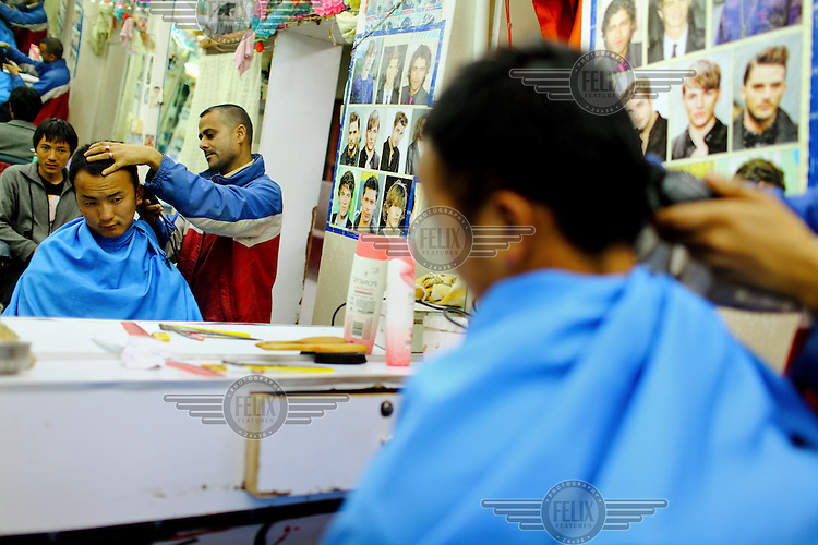 A barber cuts a boy's hair in Thimpu.