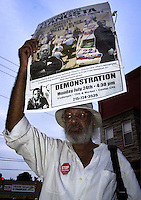 Vaul Dallas holds up a sign to protest the July 12 Philadelphia Police beating of Thomas Jones by city police officers attempting to arrest the carjacking suspect, Sunday, July 23, 2000, in Philadelphia. The beating incident was videotaped by a local television station helicopter, and broadcast around the world, shedding a bad light on the city of Philadelphia two weeks before the Republican National Convention. MANDATORY CREDIT: (Photo by William Thomas Cain/Photojournalist.cc)