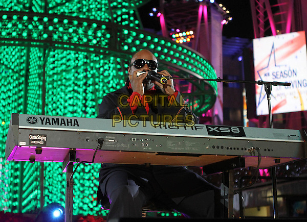STEVIE WONDER .The Holiday Tree Lighting At L.A. Live & Opening Of L.A. Kings Holiday Ice held At L.A Live,  Los Angeles, CA, USA, .4th December 2010..music concert live on stage gig half length sunglasses black red microphone harmonica  polo neck sitting playing keyboard .CAP/ADM/KB.©Kevan Brooks/AdMedia/Capital Pictures.