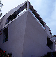 The concrete house protrudes from the hillside at a sharp angle like the prow of a ship