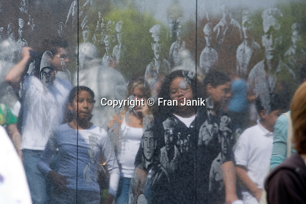 Reflections of visitors mix with the faces of soldiers as depicted on the granite surface of the Korean War Memorial in Washington D.C. in the United States.