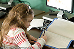 Education Elementary school Grade 2 science special female student writing in report in front of computer horizontal