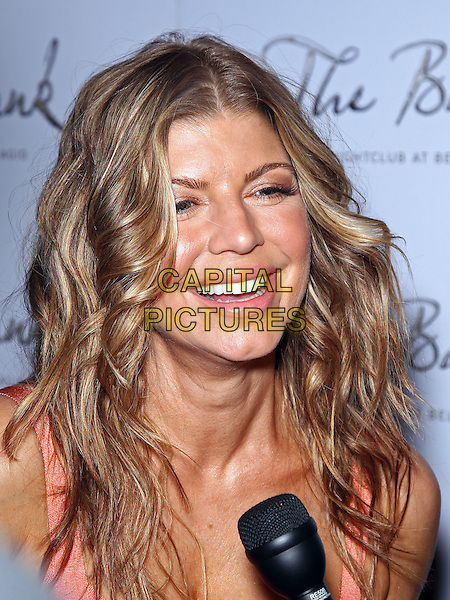 FERGIE (STACY FERGUSON OF BLACK EYED PEAS).Fergie celebrates her birthday at The Bank Nightclub inside the Bellagio Resort Hotel and Casino, Las Vegas, Nevada, USA, 25th March 2011..portrait headshot mouth open blonde hair highlights wavy interview microphone smiling .CAP/ADM/MJT.© MJT/AdMedia/Capital Pictures.