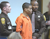 Sniper suspect Lee Boyd Malvo, center, is surrounded by deputies as he is brought into court to be identified by a witness during the trial of sniper suspect John Allen Muhammad in Courtroom 10 at the Virginia Beach Circuit Court in Virginia Beach, Virginia, Wednesday October 22, 2003.  Witness Muhammad Rashid, a Maryland liquor store owner, identified Malvo as the man who shot him. <br /> Credit: Davis Turner - Pool via CNP