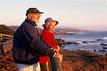 Mature adult tourist couple watching the sunset over Pacific Ocean from Leffingwell Landing, Cambria, California