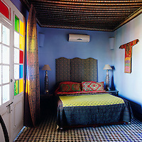 The blue bedroom has a decoratively painted ceiling and the sun shines through stained glass doors. Two ornate lamps stand either side of the double bed. A padded folding screen doubles as a headboard and the bedroom is a mix of various colours and patterns.