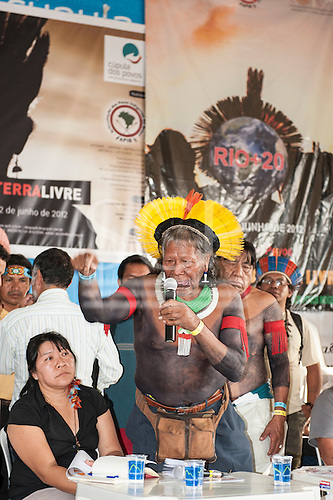 Kayapo Chief Raoni Txucarrhamae speaks to a packed audience about his people's opposition to the construction of hydroelectric dams, especially Belo Monte; to the left is indigenous lawyer Joenia Batista de Carvalho, a Wapichana Indian. The People's Summit at the United Nations Conference on Sustainable Development (Rio+20), Rio de Janeiro, Brazil, 16th June 2012. Photo © Sue Cunningham.
