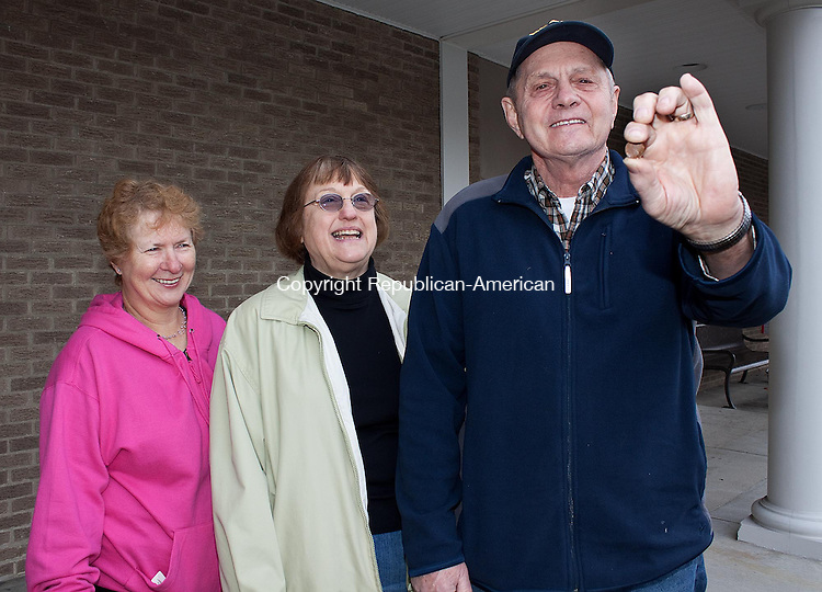 SOUTHBURY CT.-16 NOVEMBER 2011 111611DA01-  Ed Wildman holds a penny that he found on his walk at the Southbury Plaza Wednesday with his cousin, Gail Bresson, left, and his former grade school classmate,  Jean Harold. The three walkers all of Southbury have an ongoing contest to see who can find the most change while on their daily walk. Last year Wildman found over $30 in change, which he gave to a local charity. <br /> Darlene Douty Republican American.