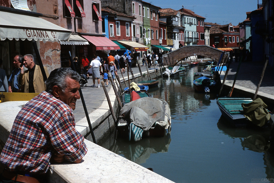 A local man scans the scenery of a Burano canal, Venice, Italy.