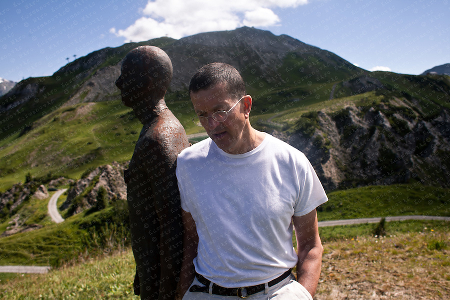 """British artist Antony Gormley stands beside one of his """"Horizon Field"""" sculptures during his exhibition opening in Lech July 31, 2010. The landscape installation made for the Kunsthaus Bregenz consists of 100 life-size, solid cast iron figures of the human body spread over an area of 150 square kilometres in the Alps forming a horizontal line at 2,039 meters above sea level."""