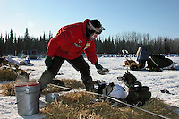 Aily Zirkle passes a bowl of steaming meat and kibble stew to her dogs at Nikolai. Photo by Jon Little.