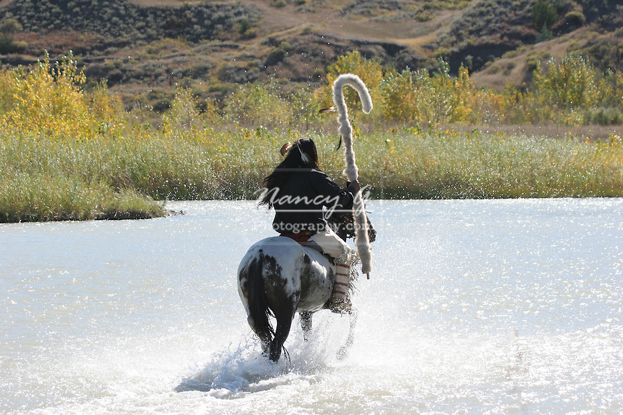 A Native American Sioux Indian on horseback riding his pony with a staff across a river in South Dakota