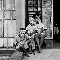 Three children wearing animal masks sit outside a shop on Hadfield Road in Hillbrow.