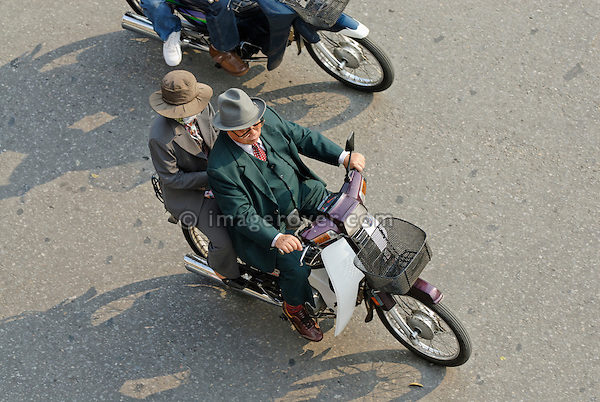 Asia, Vietnam, Hanoi. Hanoi old quarter. Elderly vietnamese couple, wearing suit and hat, riding on a small motorbike through Hanoi.