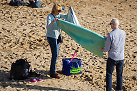 WEATHER PICTURE WALES<br /> A couple unpack on the beach during the unusually warm weather in Langland Bay near Swansea, Wales, UK. Wednesday 27 February 2019