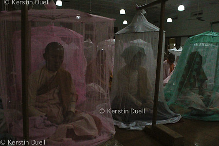 Daily routine in the Mahasi Sasana Yeiktha centre: Nuns and lay women meditation under mosquito nets at 4 am