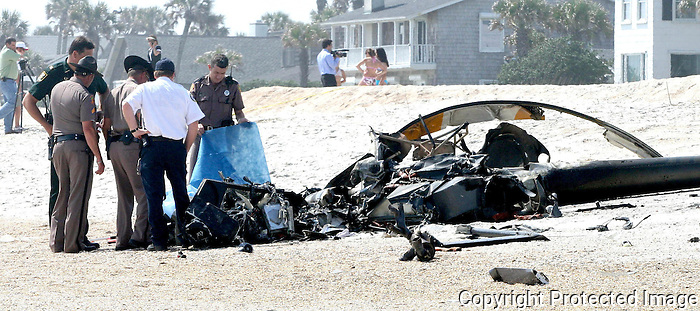 Gary Wilcox/staff... 03/27/07...A student pilot and his instructor died Tuesday when this small civilian helicopter from Silver State Helicopters at Craig Municipal Airport crashed then plunged nose-first into the sand, bounced briefly and burst into flames behind homes in the 300 block of the oceanfront Ponte Vedra Boulevard near the San Diego Road public beach access.last Tuesday. (03/27/07)